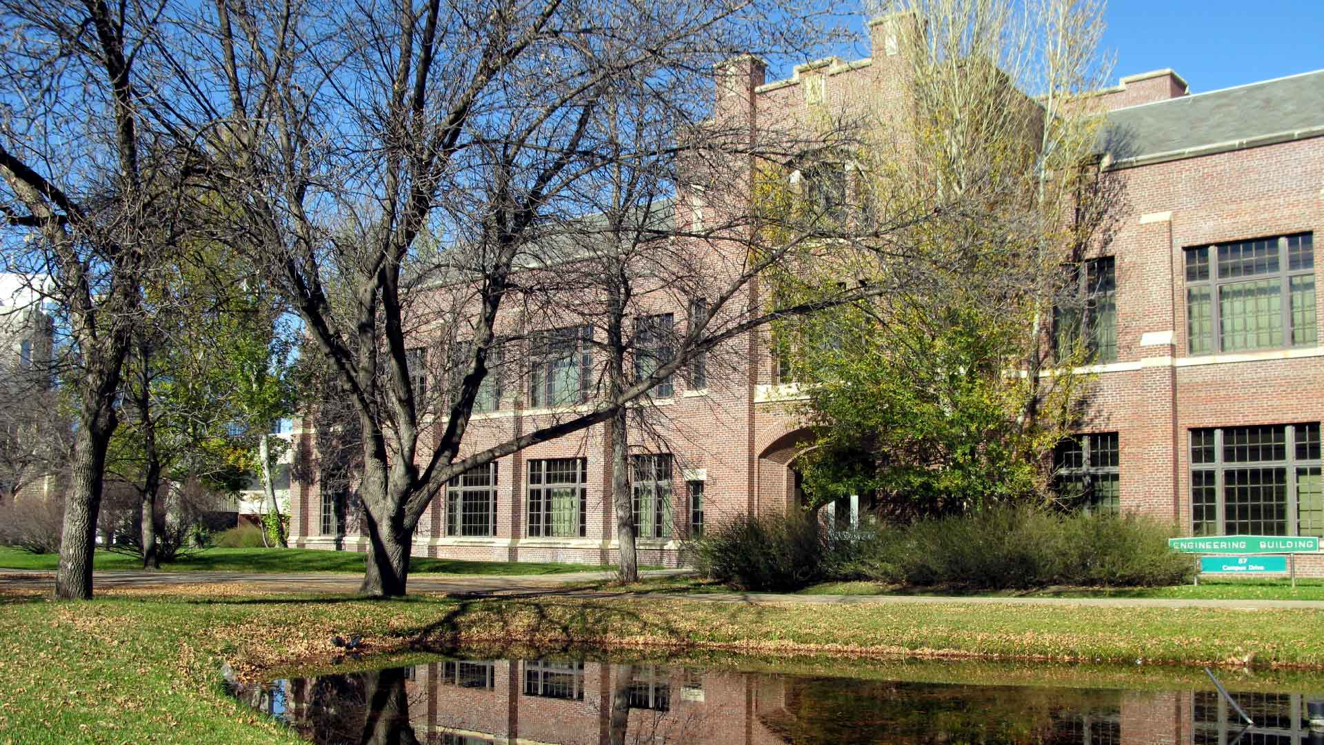 Building and pond at the University of Saskatchewan with blue skies