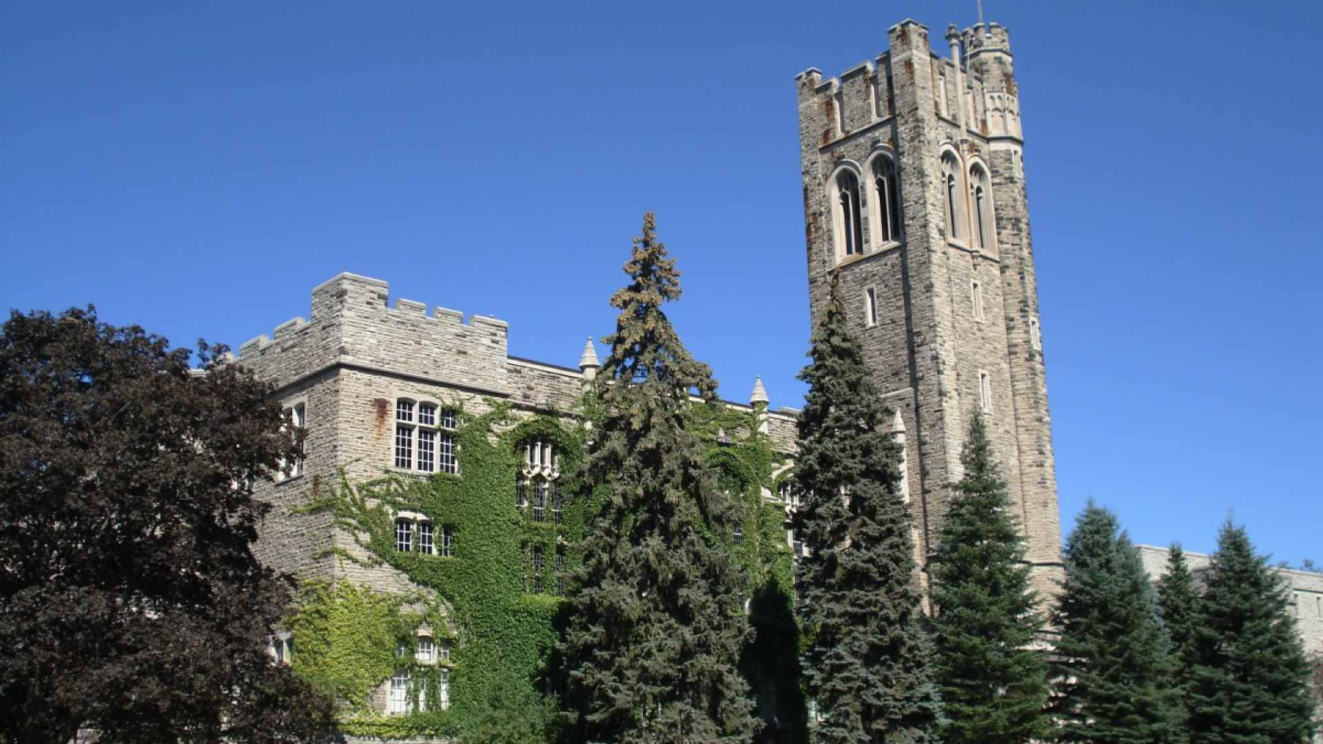 University College Building tower above trees against blue sky at University of Western Ontario